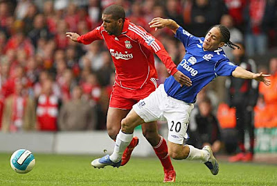 Ryan Babel of Liverpool is brought down by Steven Pienaar of Everton