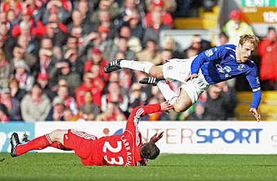 Phil Neville of Everton flies through the air after being tackled hard by Jamie Carragher of Liverpool