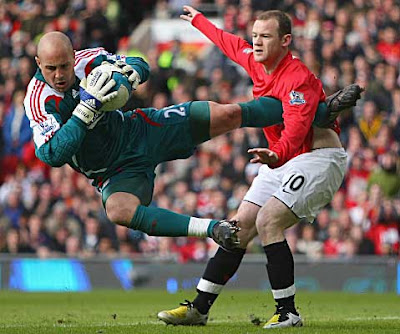Wayne Rooney of Manchester United tangles with Liverpool goalkeeper Jose Reina during their Premier League match at Old Trafford on March 23, 2008 in Manchester, England.
