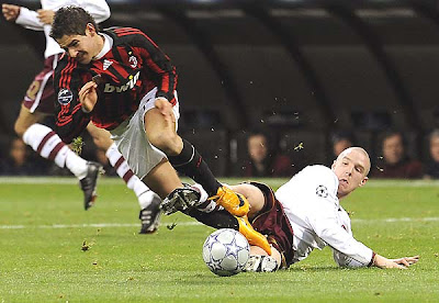 Milan's forward Pato (L) is tackled by Arsenal's defender Philippe Senderos during the first half of action.