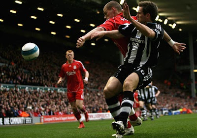 Michael Owen of Newcastle United in action with Martin Skrtel of Liverpool