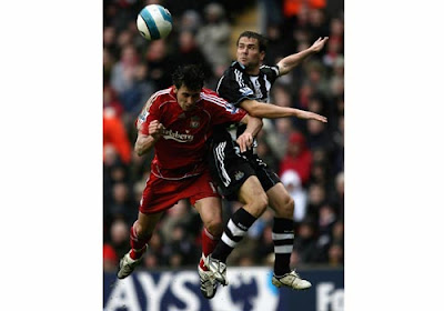 Michael Owen of Newcastle United in action with Alvaro Arbeloa of Liverpool