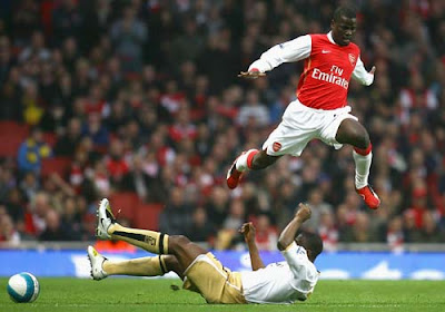 Emmanuel Eboue of Arsenal jumps over a tackle by George Boateng of Middlesbrough