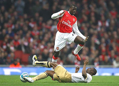 Emmanuel Eboue of Arsenal jumps over a tackle by George Boateng of Middlesbrough during their Barclays Premier League match held at the Emirates Stadium in London, England.