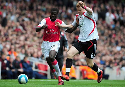 Emmanuel Eboue of Arsenal is closed down by John Arne Riise of Liverpool