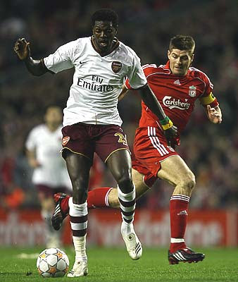 Steven Gerrard of Liverpool battles for the ball with Emmanuel Adebayor of Arsenal.