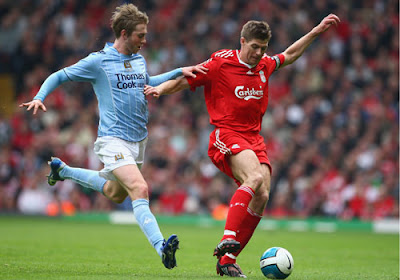 Steven Gerrard of Liverpool holds off the challenge of Michael Johnson of Manchester City