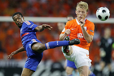 France's Patrice Evra, left, challenges for the ball with Netherlands' Dirk Kuyt.