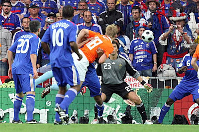 Netherlands' Dirk Kuyt, center, scores the opening goal past France's goalkeeper Gregory Coupet, rear center.