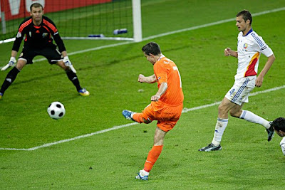 Netherlands' Robin van Persie, center, scores his side's second goal past Romania's Bogdan Lobont.