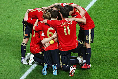 The Spain team huddles around goal-scorer Fernando Torres.