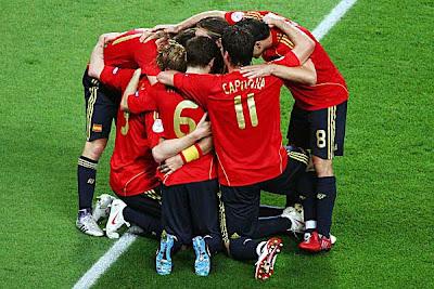 The Spain team huddles around goal-scorer Fernando Torres.