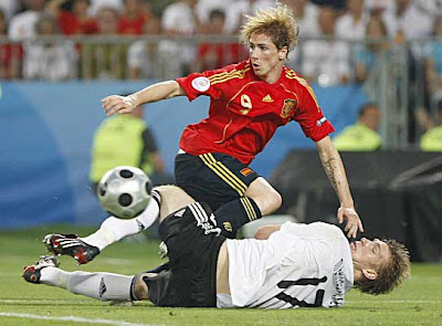 Spain's Fernando Torres (rear) is tackled by Germany's Per Mertesacker.