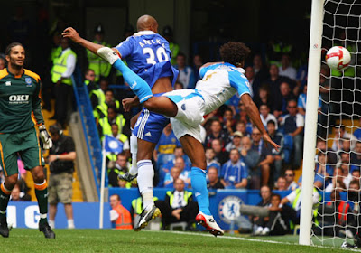 Nicolas Anelka of Chelsea outjumps Glen Johnson of Portsmouth to score the team's second goal in the first half, as Pompey goalkeeper David James looks on.