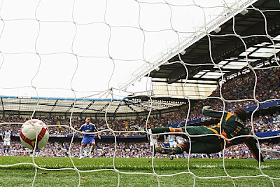 Frank Lampard scores Chelsea's third goal by beating Portsmouth goalkeeper David James from the penalty spot late in the first half.