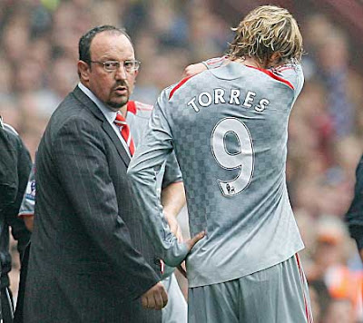 Liverpool manager Rafael Benitez checks on the condition of Fernando Torres after the striker was injured. Torres left the field.