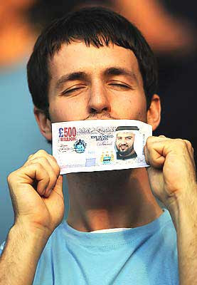 A Manchester City fan holds a fake British Pound note with the face of Sheikh Mansour bin Zayed Al Nahyan during the Barclays Premier League match between Manchester City and Chelsea at The City of Manchester Stadium in Manchester, England.
