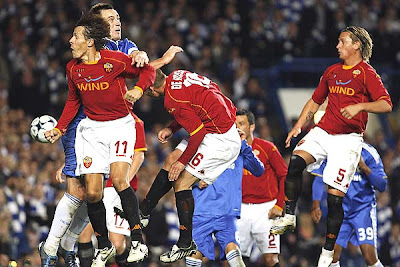 Chelsea's John Terry (2ndL) heads the ball and collides with AS Roma's Rodrigo Taddei (L) and Daniele De Rossi (C) as the ball heads into the goal in the second half