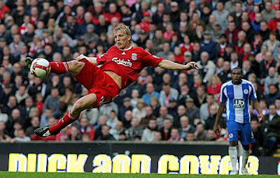 Liverpool striker Dirk Kuyt goes acrobatic to score Liverpool's winning goal. Liverpool beat Wigan 3-2.