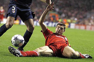 Liverpool midfielder Steven Gerrard tackles Atletico Madrid defender John Heitinga.