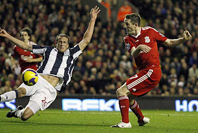 Liverpool forward Robbie Keane (right) scores past West Bromwich Albion defender Jonas Olsson during their English Premier League football match at Anfield in Liverpool, north west England.