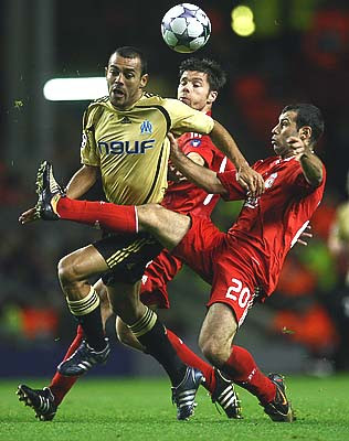 Vitorino Hilton of Marseille is challenged by Javier Mascherano (R) and Xabi Alonso of Liverpool during their UEFA Champions League Group D match at Anfield in Liverpool, England