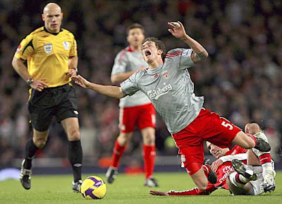 Liverpool's Daniel Agger is tackled by Arsenal's Robin van Persie. Ten-man Arsenal held on for a 1-1 draw.