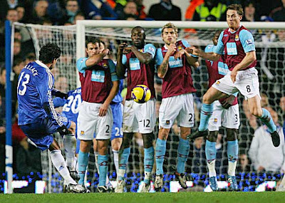 Chelsea's Michael Ballack (left) takes a free-kick as West Ham's defensive wall jumps
