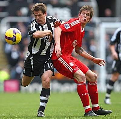 Daniel Agger of Liverpool battles with Michael Owen of Newcastle.