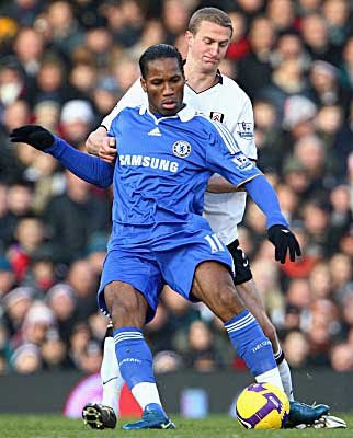 Didier Drogba of Chelsea is challenged by Brede Hageland of Fulham