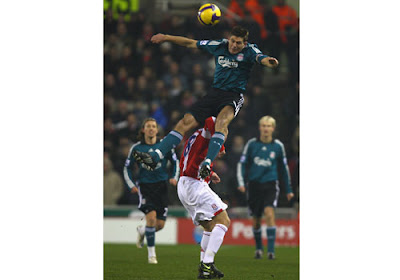 Steven Gerrard of Liverpool tangles in the air with Andy Wilkinson of Stoke City