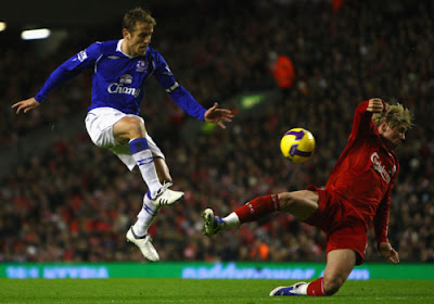 Phil Neville of Everton competes for the ball with Fernando Torres of Liverpool