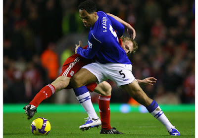 Joleon Lescott of Everton tangles with Dirk Kuyt of Liverpool