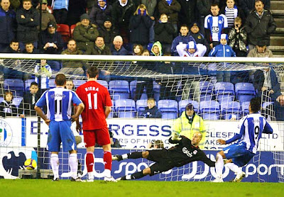 Mido of Wigan scores a penalty late in the match against Liverpool.