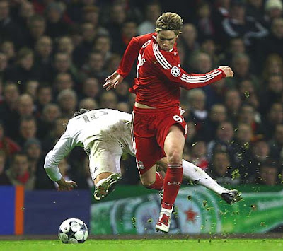 Fernando Torres of Liverpool tangles with Gabriel Heinze of Real Madrid.