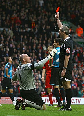 Referee Martin Atkinson sends off Brad Friedel of Aston Villa for a foul in the penalty area.