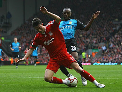 Nigel Reo-Coker of Aston Villa brings down Albert Riera of Liverpool to concede a penalty.