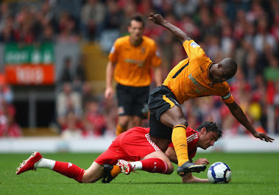Albert Riera of Liverpool tangles with George Boateng of Hull City