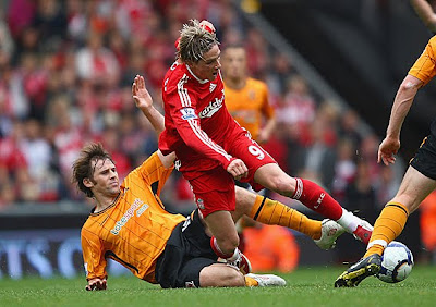 Fernando Torres of Liverpool is tackled by Kevin Kilbane of Hull City.