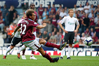Alessandro Diamanti of West Ham slip as he scores a penalty against Liverpool.