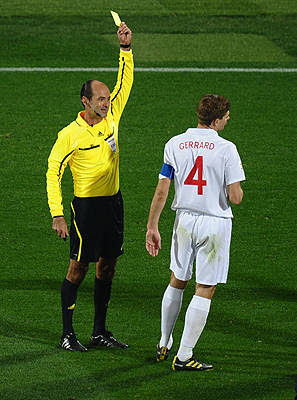Brazilian referee Carlos Simon gives a yellow card to England's defender Jamie Carragher as England's midfielder Steven Gerrard stands by during their Group C first round 2010 World Cup football match on June 12, 2010 at Royal Bafokeng stadium in Rustenburg.
