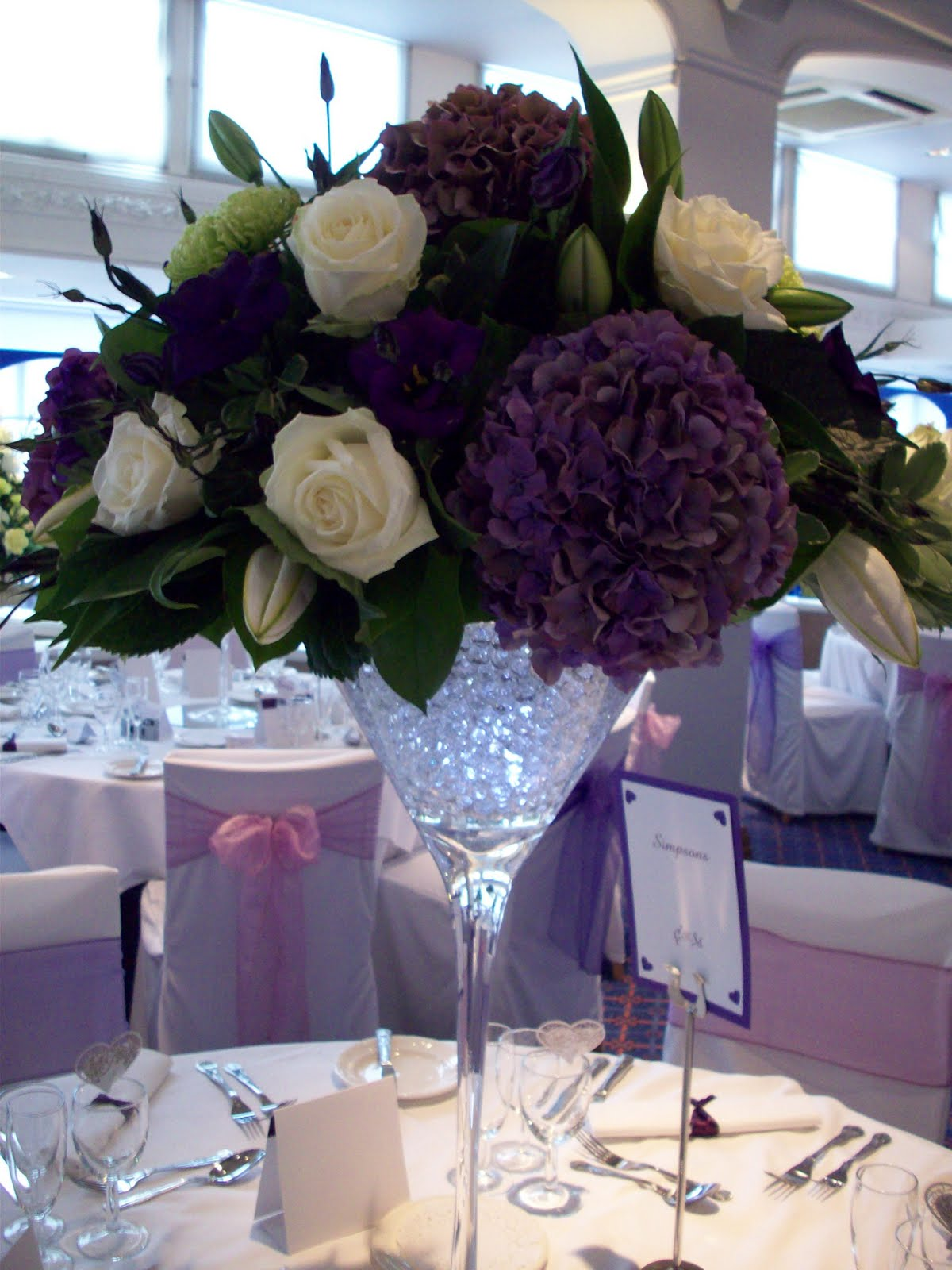 Florian designer florist wedding flower specialist purple plum martini vases filled with light sparkled pearls held huge domes of flowers with amazing coloured mottled hydrangeas that blended all the shades of purple reviewsmspy