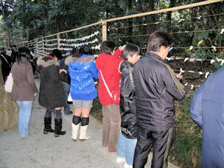Tying sacred lots in Meiji Shrine.