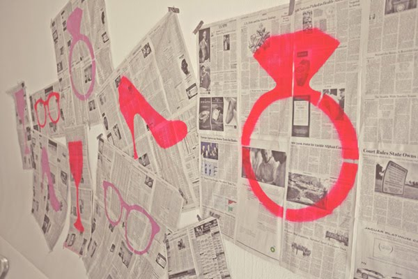 paint black centers in daisies and spray paint newspaper with hot pink
