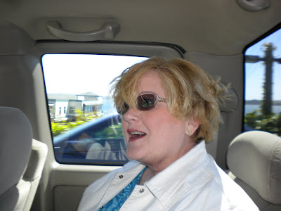 Gram, back in the car, hair blown all to pieces