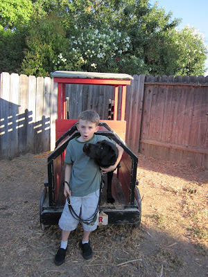 Dagan standing in the engine area of the wooden car, looking up at Luke