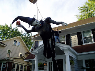 A giant witch being lifted onto a roof by a crane