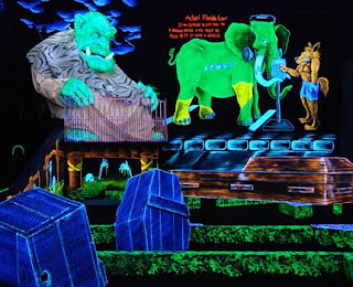 Monsters and coffins decorate a glow in the dark miniature golf course