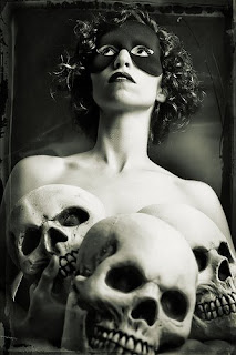 black and white photo of a masked and topless woman holding three skulls