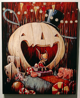 Painting of Pinocchio sitting in the mouth of a giant jack-o-lantern, by Brandi Milne